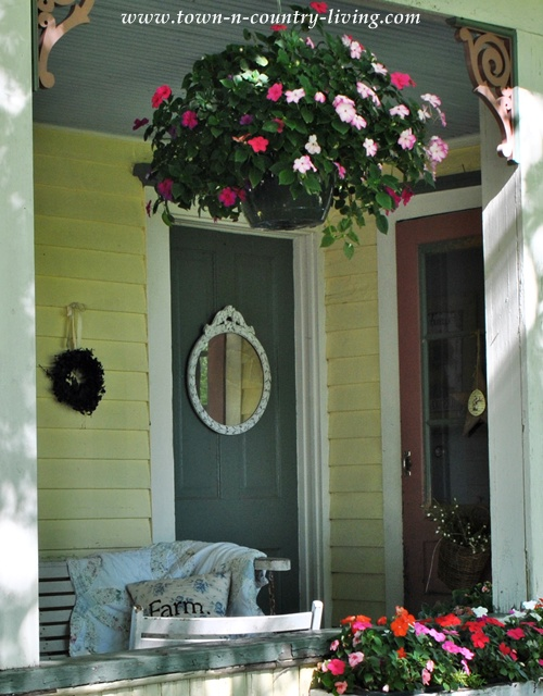 Hanging basket of impatiens on a farmhouse porch