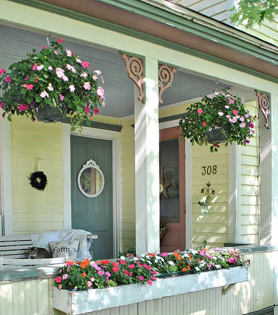 Farmhouse Front Porch with Hanging Flower Baskets via Town and Country Living