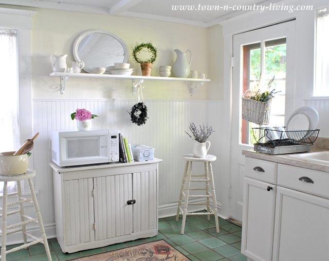 Bead board and open shelving creates a farmhouse style kitchen via Town and Country Living