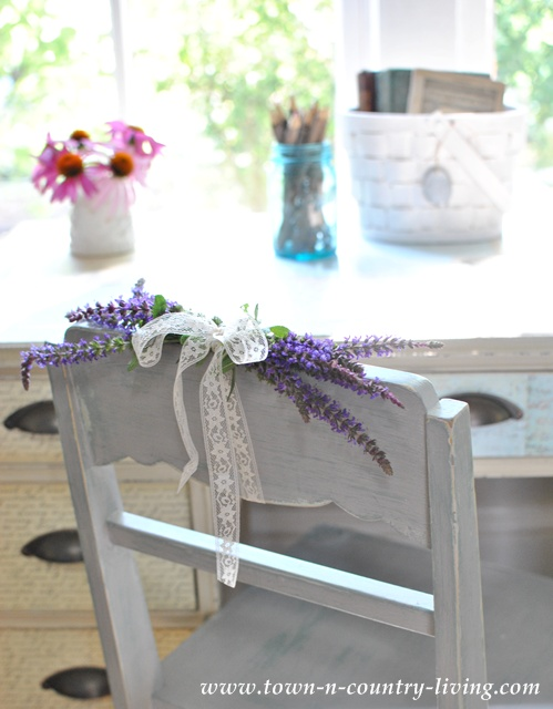Flowers tied to a painted cottage chair via Town and Country Living