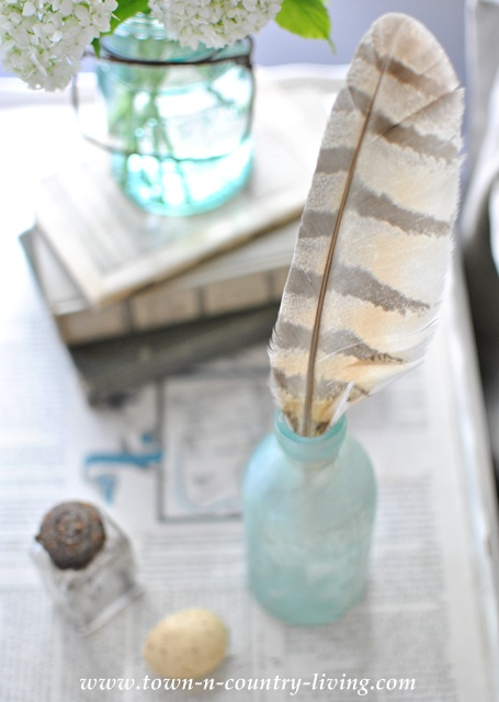 Feather in an aqua bottle for simple decorating - Town and Country Living