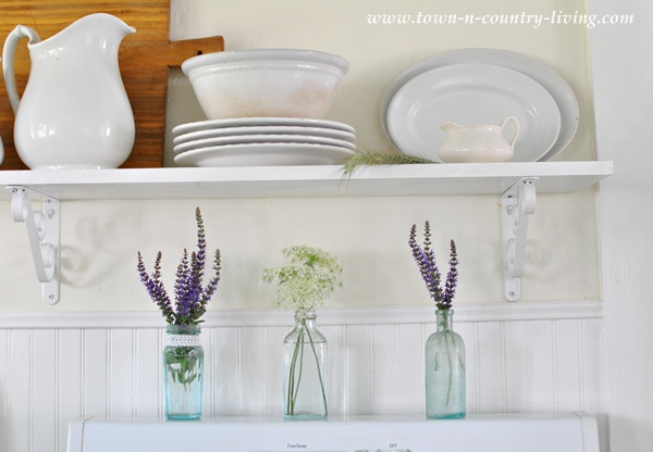 White ironstone and aqua bottles in a farmhouse kitchen via Town and Country Living