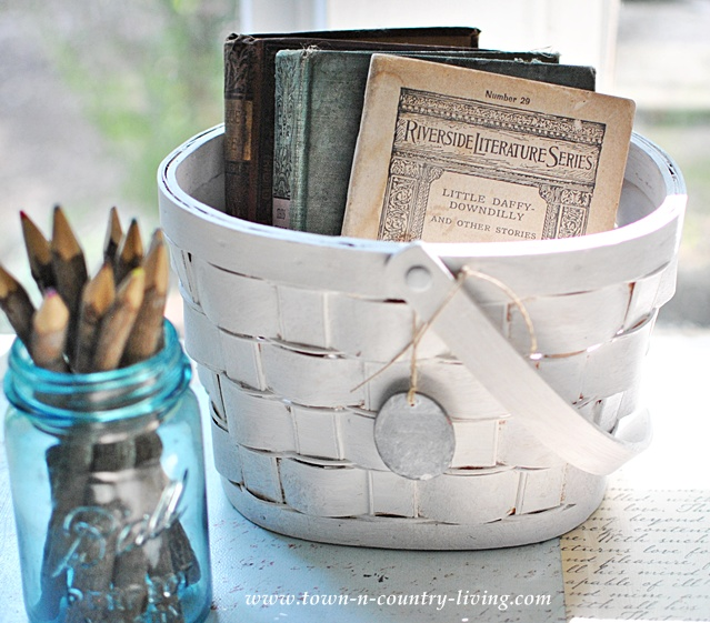 White painted basket holds vintage books via Town and Country Living
