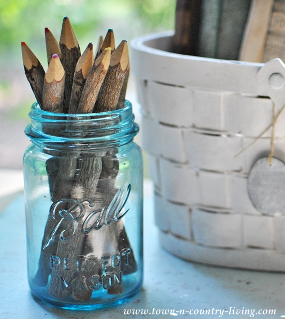 Blue Ball mason jar filled with branch type pencils via Town and Country Living