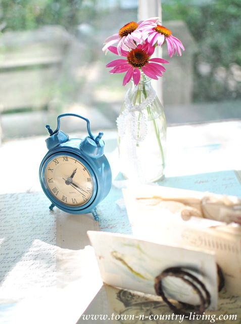 Blue clock and vintage letters on a decoupaged desk via Town and Country Living