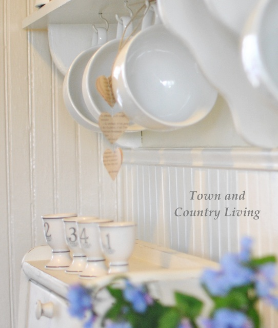Oversize coffee mugs hanging from a kitchen shelf via Town and Country Living