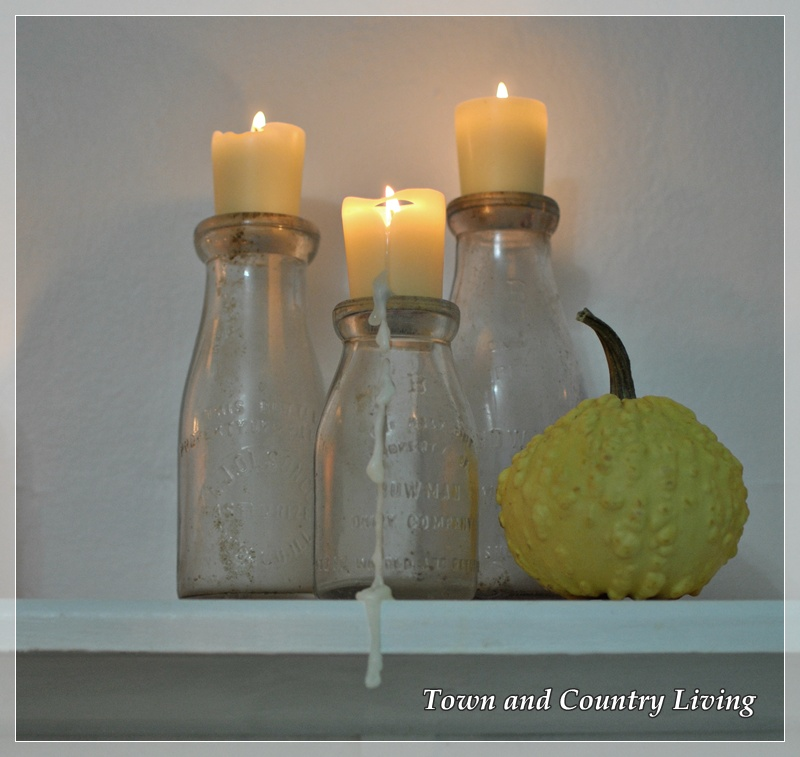 Milk bottles with votive candles via Town and Country Living
