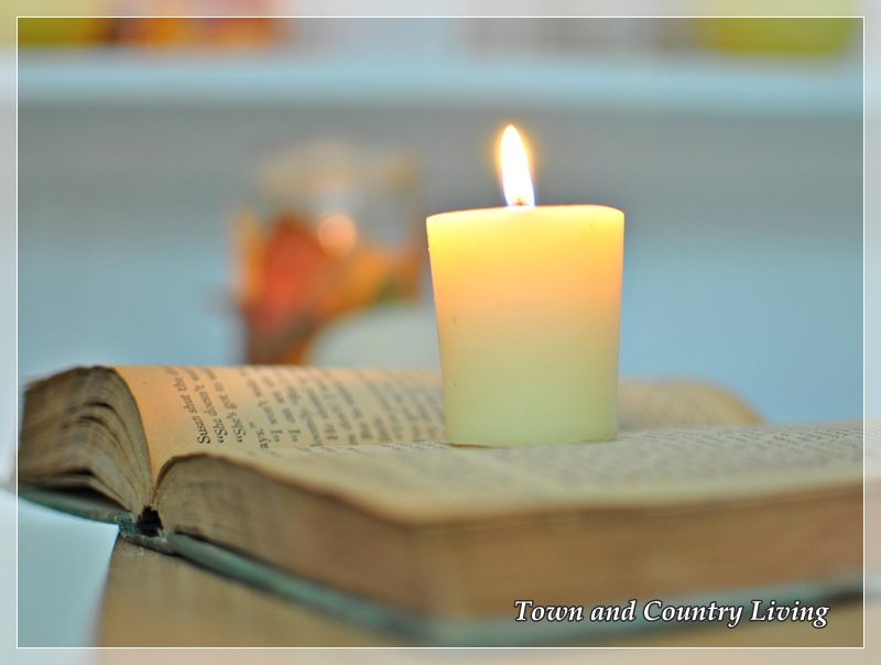 Simple votive candle on a vintage book via Town and Country Living