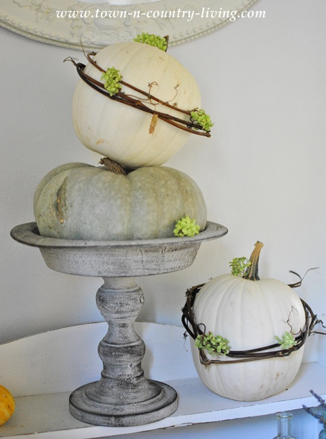 Stacked Pumpkins on Pedestal with Grapevine Wreaths via Town and Country Living