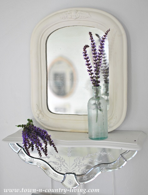 Vintage mirror on a mirrored shelf via Town and Country Living