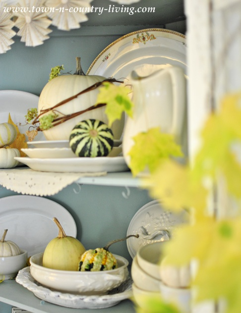 White ironstone and pumpkins in a Farmhouse Fall Hutch via Town and Country Living