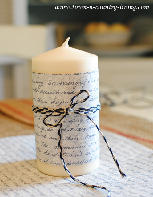 Decorate a white pillar candle with scrapbook paper and multi-colored twine