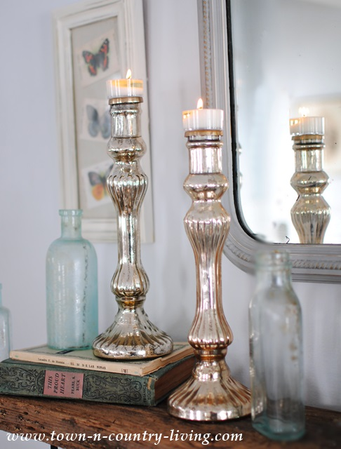 Mercury candles paired with aqua bottles and vintage books