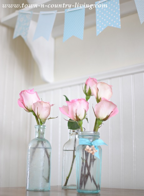 Pretty pink roses in vintage aqua bottles