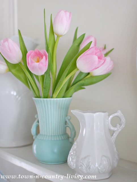 A flea market vase holds a spring bouquet of pink tulips