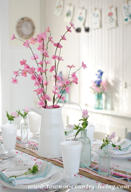 Spring decorating with pink blossoms and aqua bottles