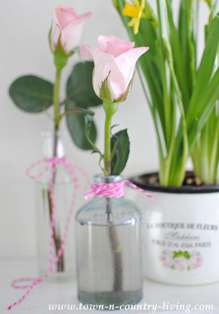 Pink roses in vintage aqua bottles