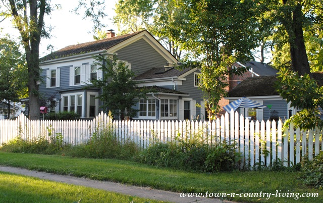 White Picket Fence Wraps around Blue Clapboard House