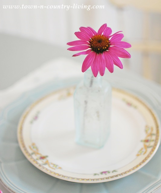 Single flower in aqua vase makes a pretty statement at a simple Summer table setting.