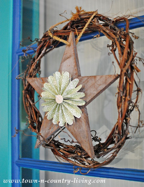 Grapevine wreath with wooden star decorates a farmhouse front door for Fall