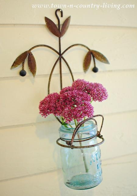 Flowering sedum gets tucked into blue Atlas jar on a farmhouse front porch