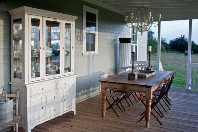 Back porch with farmhouse table and white china cabinet