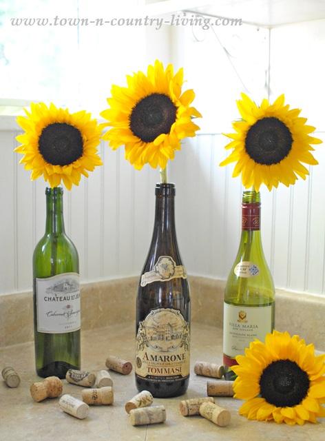 Sunflowers arranged in wine bottles