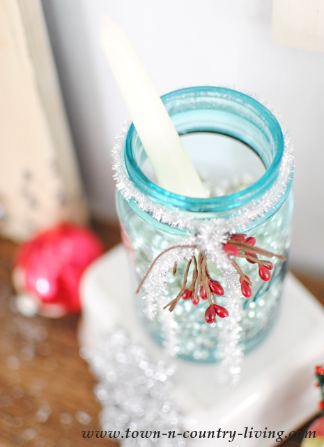 Blue mason jar filled with silver beads and a simple candle creates pretty Christmas decor.