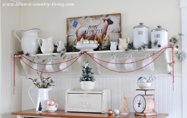 DIY Christmas Vignette. Create a festive mood by stringing red glass beads on open kitchen shelving.