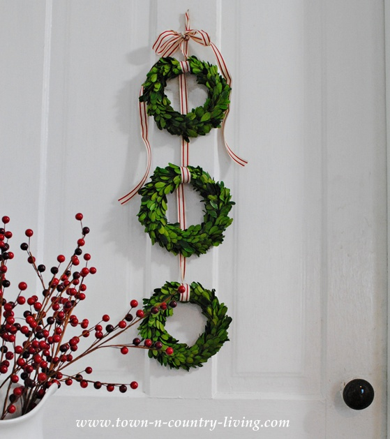 DIY Christmas Decor. String a trio of boxwood wreaths to make an easy and attractive wall hanging.