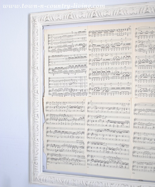 A painted frame and book pages creates the backdrop for custom wall art.