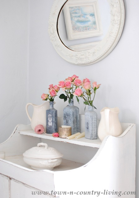 Farmhouse dry sink displays white ironstone and painted gray bottles filled with spray roses
