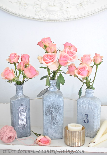 Painted bottles serve as pretty vases for sprays of roses
