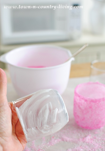 """Paint"" a glass tumbler with Mod Podge before adding pink Epsom salts."