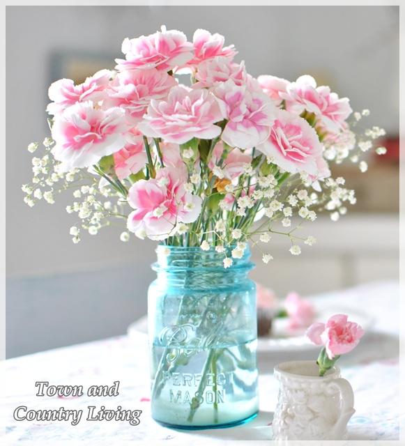 Pink carnations in blue mason jar make a happy centerpiece