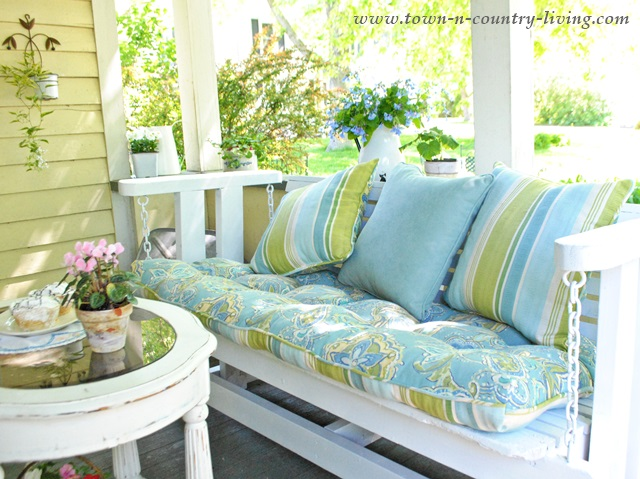 Blue and Green Pillows and Cushions soften a Porch Glider