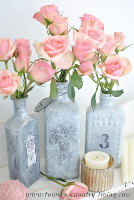 Vintage bottles painted gray and embellished with pink spray roses
