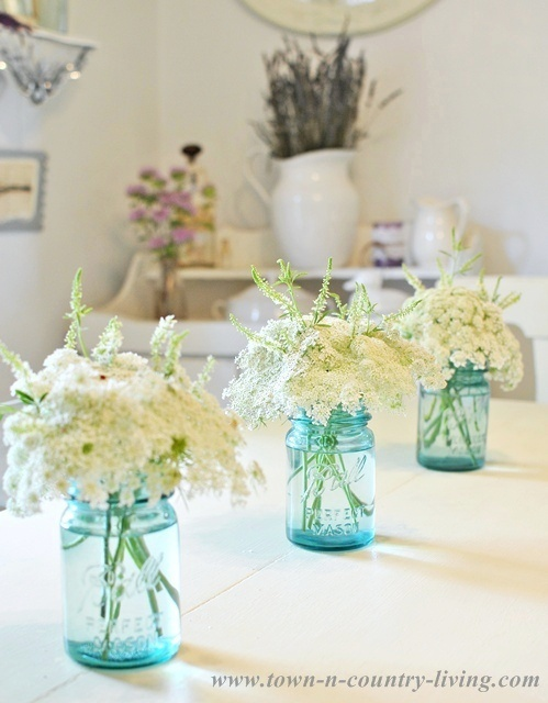 For a simple centerpiece, tuck white wildflowers into blue mason jars