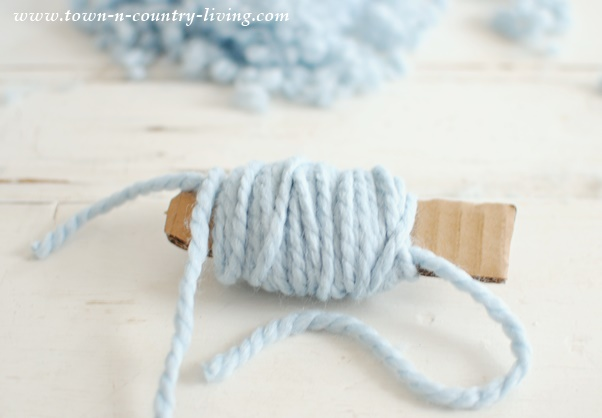Wind yarn around a cardboard guide to make your own pom poms.