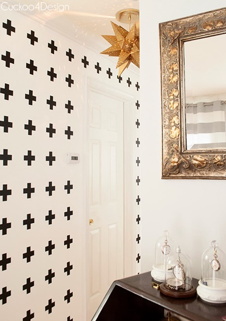 Unique crosses decorate a single wall in the hallway