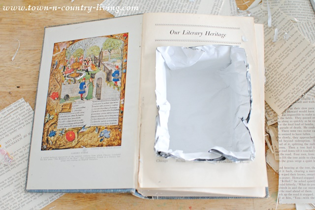 To make a book planter, cut a rectangular hole in the book and line it with parchment paper. Fill with dirt and a plant.