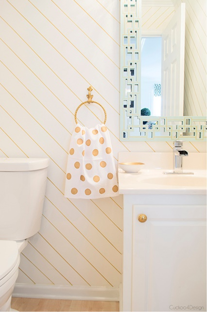 Powder room with diagonal stripes and gold polka dots. See the full home tour!