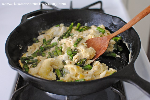 Scrambling eggs for a farmhouse breakfast in an iron skillet with a roux spoon handcrafted from hickory wood.
