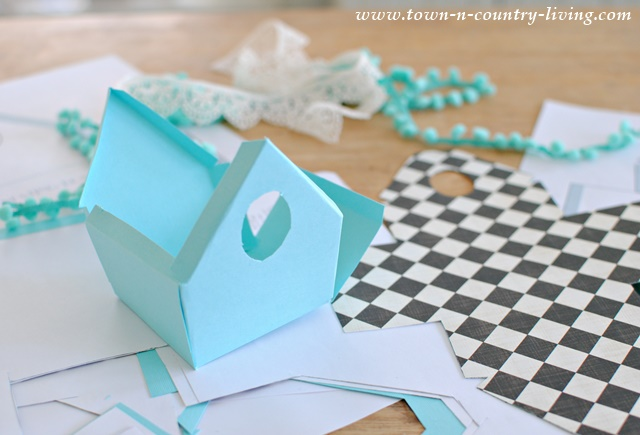 How to make paper birdhouses using scrapbook paper and decorative trim.